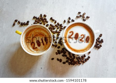 Goodbye 2019 Hello 2020 holidays food art theme coffee cup with number 2020 on frothy surface, another one with 2019 at the bottom of cup over grey cement background with coffee beans. (top view)
