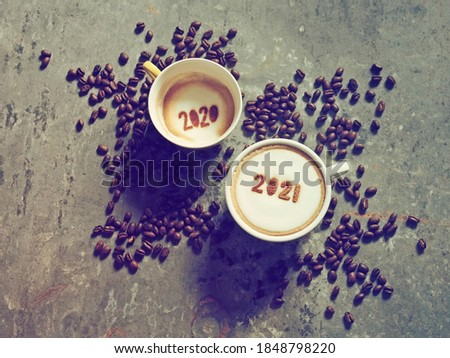 Goodbye 2020, Hello 2021 holidays food art theme coffee cups with number 2021 and 2020 on frothy surface flat lay on grey cement background with coffee beans. Holidays food art for Happy New Year.