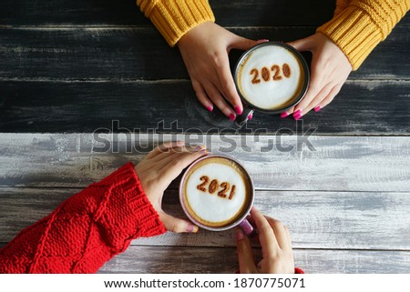 Goodbye 2020, Hello 2021 theme coffee cup with number 2021 on frothy surface in female hands holding over grey wooden plank and opposite side with number 2020 on frothy surface over black wooden table
