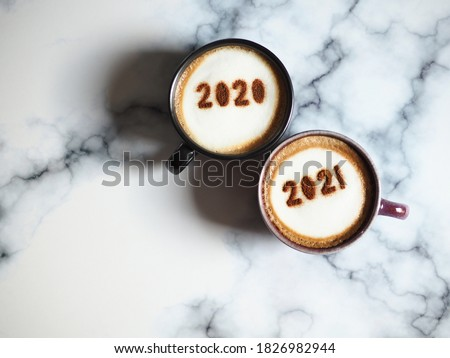 Goodbye 2020, Hello 2021 theme coffee cups with number 2020 and 2021 on frothy surface flat lay on blurred marble background. Holidays food art concept for active days. (top view, space for text)