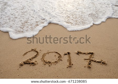 Goodbye 2017 years. Hand writing 2017 on sand beach with wave is coming. New year concept #671238085