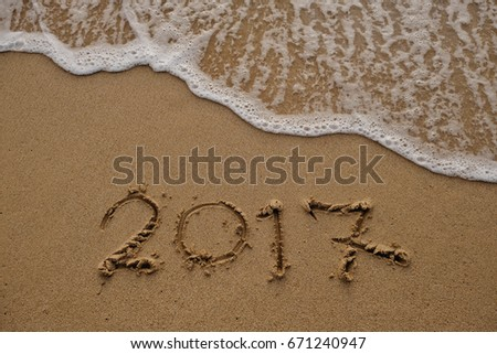 Goodbye 2017 years. Hand writing 2017 on sand beach with wave is coming. New year concept #671240947