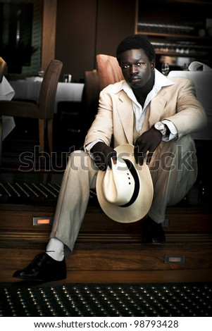 Goodlooking African Male Fashion Model Striking A Pose In A White Suit With Matching Panama Hat While Sitting On A Step Inside A Fine Dining Restaurant - stock photo