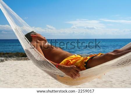 Goodlooking man, asleep in a hammock on a tropical beach.