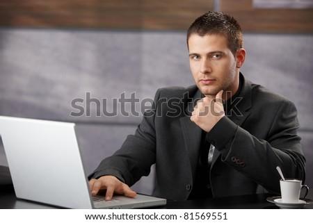 Goodlooking manager sitting at desk, using laptop in elegant office.?