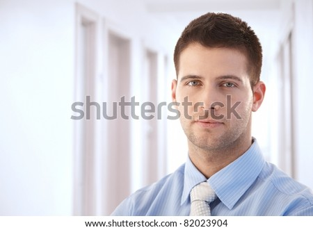 Goodlooking young businessman standing in hallway.?