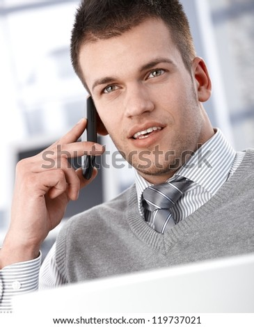 Goodlooking young businessman talking on mobile phone.
