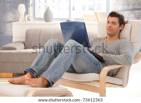 Goodlooking Young Man Relaxing At Home In Armchair ...
