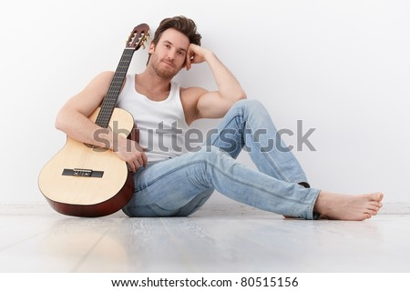 Goodlooking young man sitting by wall, holding guitar, smiling.?