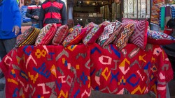 Goods:  colorful  cushions and  plaid in Morocco -  Marrakesh.   Bright red  color prevails