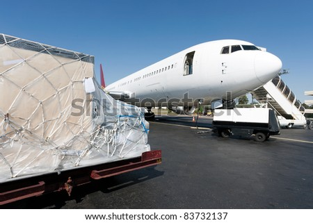 Goods waiting loaded to the plane - stock photo
