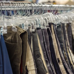 Goodwill is an American nonprofit organization and a second-hand store that creates jobs. Items donated to the thrift store are resold to the public. Retail coat hangers merchandised on racks in store