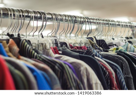 Goodwill is an American nonprofit organization and a second-hand store that creates jobs. Items donated to the thrift store are resold to the public. Retail coat hangers merchandised on racks in store Stockfoto ©
