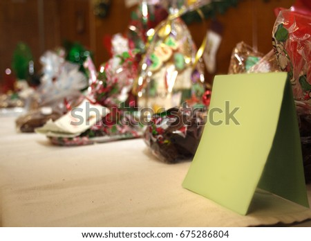 Stock Photo goody bags of christmas or holiday candy blurry in background with blank green card