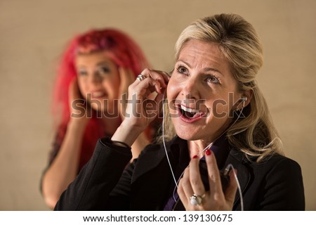 Goofy Caucasian lady with mp3 player and annoyed teenager #139130675