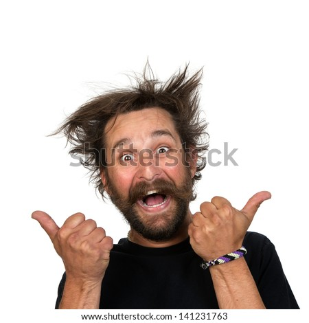 Goofy young man grins at the camera while giving a thumbs up sign. Isolated on white background.