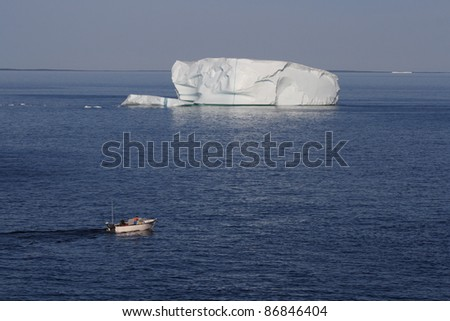 GOOSE COVE, CANADA – JULY 26: Men in a motorboat among icebergs on July 26, 2011 in Goose Cove, Newfoundland. Icebergs from Greenland drift past Newfoundland each spring and summer.