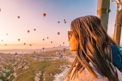 Goreme Cappadocia Turkey July 2018, hot air balloons during Sunrise over the fairytale landscape hills of Kapadokya, young woman in hot air balloon