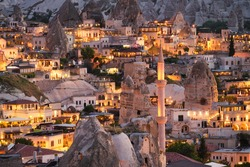Goreme, Cappadocia, Turkey. View of the evening city from the mountain. Bright evening city. Landscape in the summertime. UNESCO heritage. Vacation and tourism.