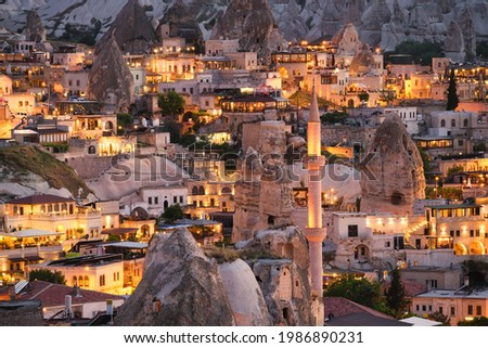 Goreme, Cappadocia, Turkey. View of the evening city from the mountain. Bright evening city. Landscape in the summertime. UNESCO heritage. Vacation and tourism. Foto stock ©