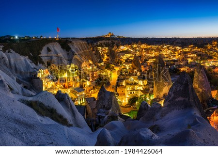 Goreme, Cappadocia, Turkey. View of the evening city from the mountain. Bright evening city and clear sky. Landscape in the summertime. UNESCO heritage. Vacation and tourism. Foto stock ©