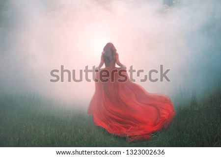 gorgeous amazing wonderful scarlet red dress with a long flying waving train, a mysterious girl with red curly hair runs away into a thick white mist and forest haze over the green summer grass