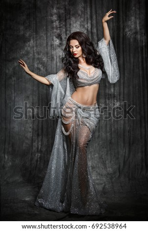 Gorgeous arabian woman bellydancer dancing in white bellydance costume over black studio background. Sexy turkish belly dancer posing in bridal baladi dress with jewelry.  #692538964