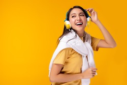 Gorgeous asian woman hanging sweater on shoulder and listening music in headphones and singing on yellow background. Charming girl dancing. Attractive lady enjoying favorite song. copy space