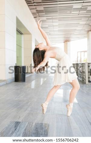 Gorgeous ballerina rehearsing dance routine on street #1556706242