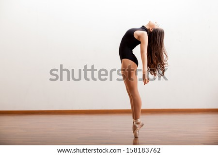 Gorgeous ballet dancer maintaining balance during a dance routine in a studio