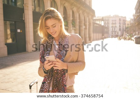 gorgeous beautiful young woman with blonde hair messaging on the smart-phone at the city street background. pretty girl having smart phone conversation in sun flare.