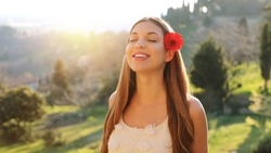 Gorgeous beautiful young woman with long hair and red flower on ear enjoying breathing fresh air in nature. Pretty smiling girl relaxing outside enjoying fresh air on summer spring season.