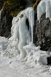 Gorgeous big icicles hanging from a cliff at Stowe ski resort in Vermont. Mid April Spring conditions at sunny day