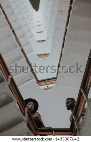 Gorgeous black couple looking form upstairs to the camera. Fine art portrait of boy and girl in love with geometric background. Wait Stairs.