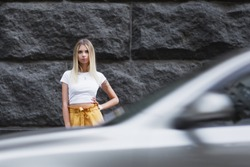 Gorgeous blond girl wearing yellow pants and white t-shirt, posing in front of the car. Architecture building in the city. Street fashion concept. Modern fashion.