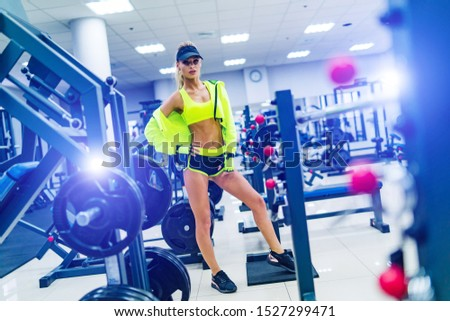 Gorgeous blonde woman is warming up and doing workout at a gym looking straifht in front of her. She wears bright sports wear and a cap