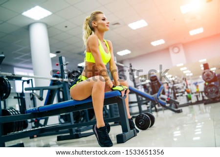 Gorgeous blonde woman is warming up and doing workout at a gym looking straifht in front of her. She wears bright sports wear. Training and healthy lifestyle.