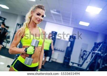 Gorgeous blonde woman is warming up with a dumbbell and doing workout at a gym looking in camera. She wears bright sports wear. Nice figure and long legs. Blurred background.