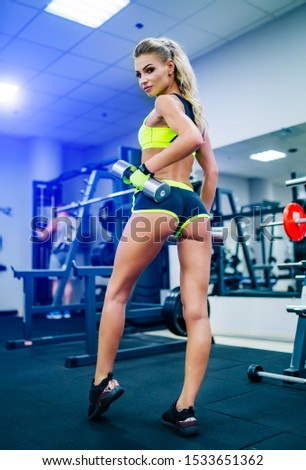 Gorgeous blonde woman is warming up with dumbbell and doing workout at a gym looking from her back. She wears bright sports wear. Nice figure and long legs.
