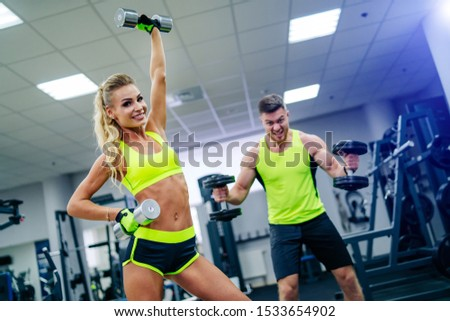 Gorgeous blonde woman is warming up with dumbbells and doing workout at a gym looking in camera. She wears bright sports wear. Nice figure and long legs. Strongman, bodybuilder has workout on the back