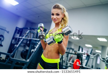 Gorgeous blonde woman is warming up with dumbbells and doing workout at a gym looking in the camera. She wears bright sports wear. Nice figure and long legs. Fitness belly.