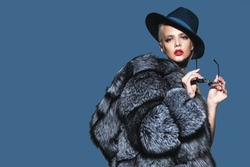 Gorgeous blonde woman posing in luxurious fur coat and a hat. Fashion, beauty. Studio shot.
