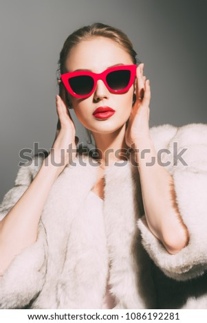 Gorgeous blonde woman posing in luxurious fur coat and pin-up sunglasses. Fashion, beauty. Studio shot. #1086192281
