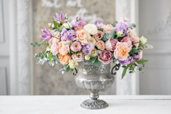 Gorgeous bouquet of different flowers. floral arrangement in vintage metal vase. table setting. lilac and peach color