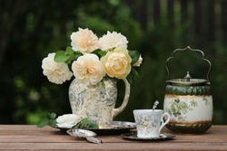 Gorgeous bouquet of fresh roses in old antique faience, ceramic, porcelain pitcher, floral pattern with golden on round aged plate, china tea cup with spoon, biscuit barrel on wooden table in garden