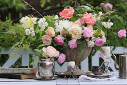 Gorgeous bouquet with colourful flowers on old aged, weathered metal vase, planter, silver plate coffee set on table, garden background, outdoors and space, floral composition, vintage style, daylight