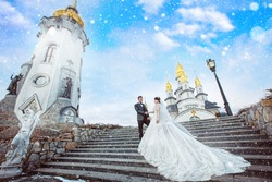 gorgeous bride and groom stand on the stairs in front of the church. happy newlywed couple hugging in winter park after sacred wedding ceremony, romantic tender moment