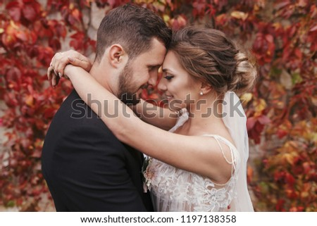 Gorgeous bride and stylish groom gently hugging and smiling at wall of autumn red leaves. Happy sensual wedding couple embracing. Romantic moments of newlywed #1197138358