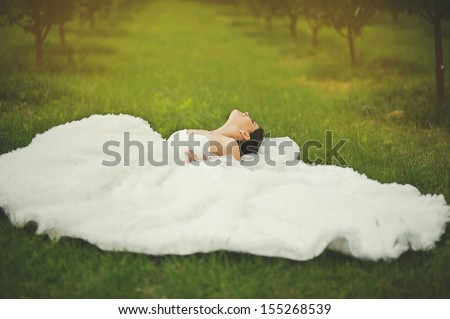 gorgeous  bride laying in garden, summertime