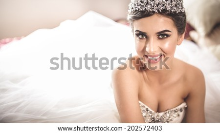 Gorgeous bride portrait in her wedding dress wearing tiara. Beautiful bridal makeup and hairstyle and hair accessories. Bride to be smiling portrait